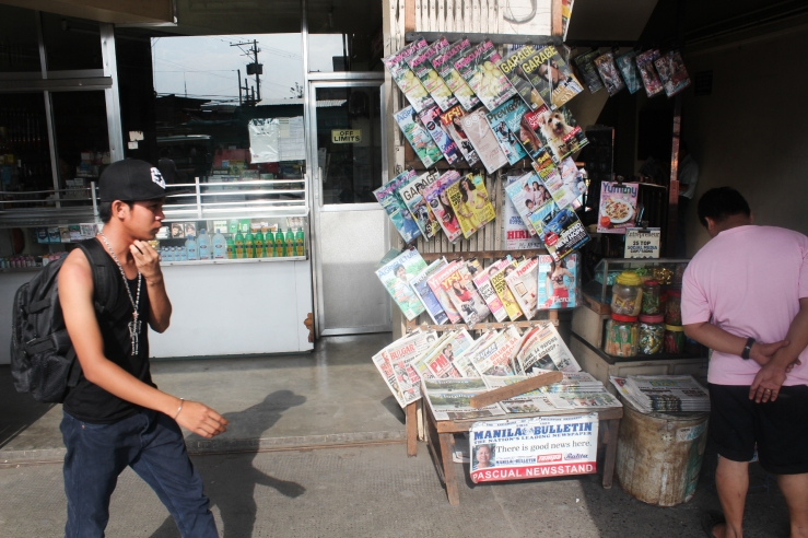 A typical newspaper stand in the Philippines, with people barely taking a glance on what's news for today. (Mick Basa)